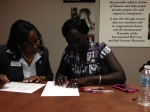 Rhoda Naylera Gatlek works with American Red Cross caseworker Dena Howard.