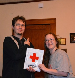 David Larrick points to one of the new smoke detectors installed in their home as he and Rachel hold the packet of fire safety information provided by the American Red Cross.